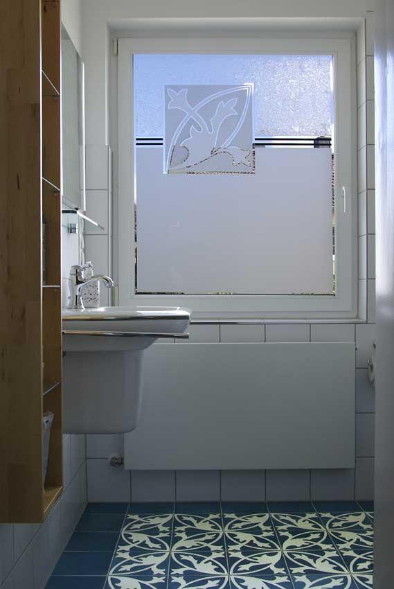 Ein Fenster in einem Badezimmer mit einem Muster, dass das Muster der Fliesen wiedergibt und teilweise matt gesandstrahlt ist oder ein Eisblumenmuster hat.
