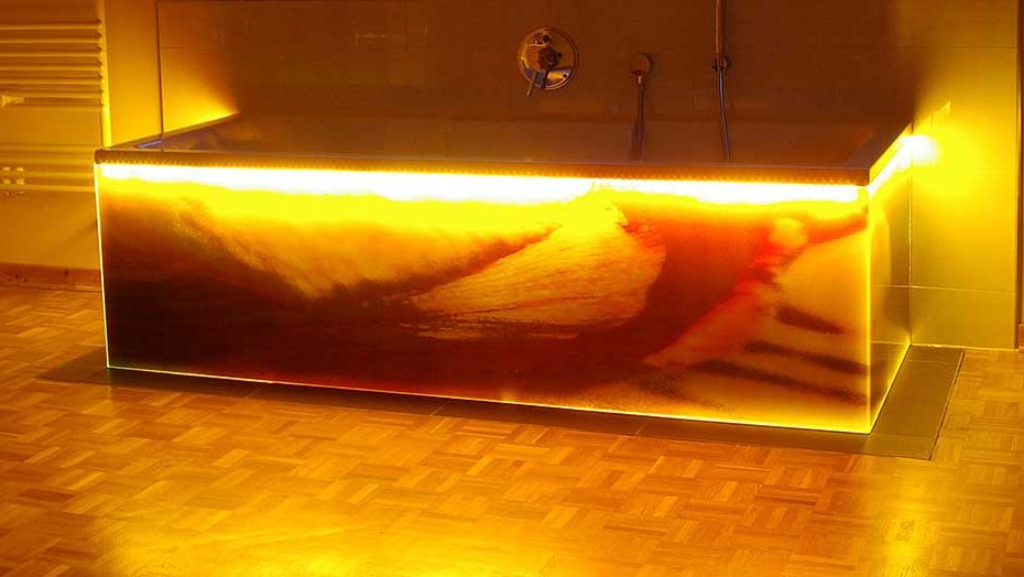 Freistehende Badewanne mit einem Glasunterbau und einer stimmungsvollen LED Beleuchtung unterhalb des Wannenrandes. Die Glasflächen sind aus bedrucktem Sicherheitsglas. Aufnahme bei Nacht.