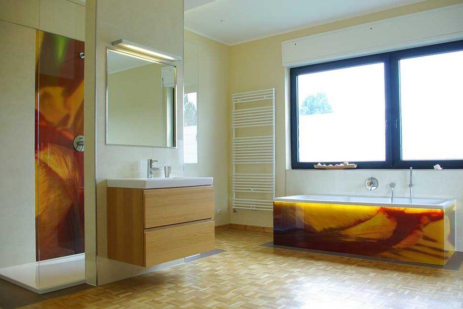 Blick ins Bad mit der farbig bedruckten ESG- Duschrückwand im Hintergrund und der Badewanne mit einem Unterbau, aus bedrucktem Sicherheitsglas in rot und orangenen, künstlerisch gestalteten Entwurf.