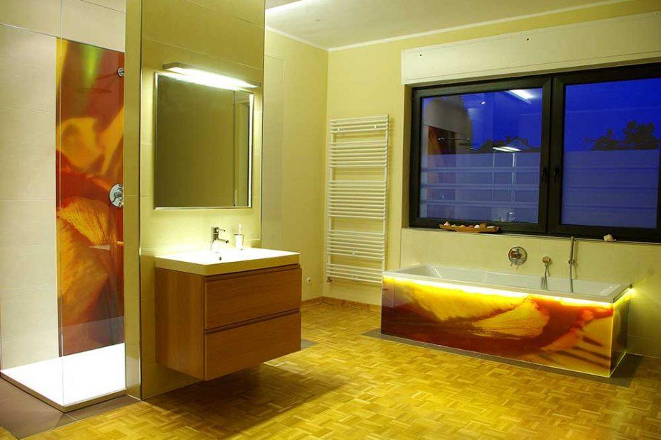 Bild des Badezimmers am Abend. Hier kommt die besondere LED Beleuchtung am Badewannenrand an den Glasflächen besonders gut zur Geltung.