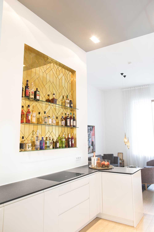 Eine edle moderne Bar mit 3 Abstellflächen für Flaschen, bestehend aus vielen mit Facetten geschliffenen aufgeklebten goldenen Antikspiegel Teilen in einem Rahmen aus Messing, eingelassen in die Wand.