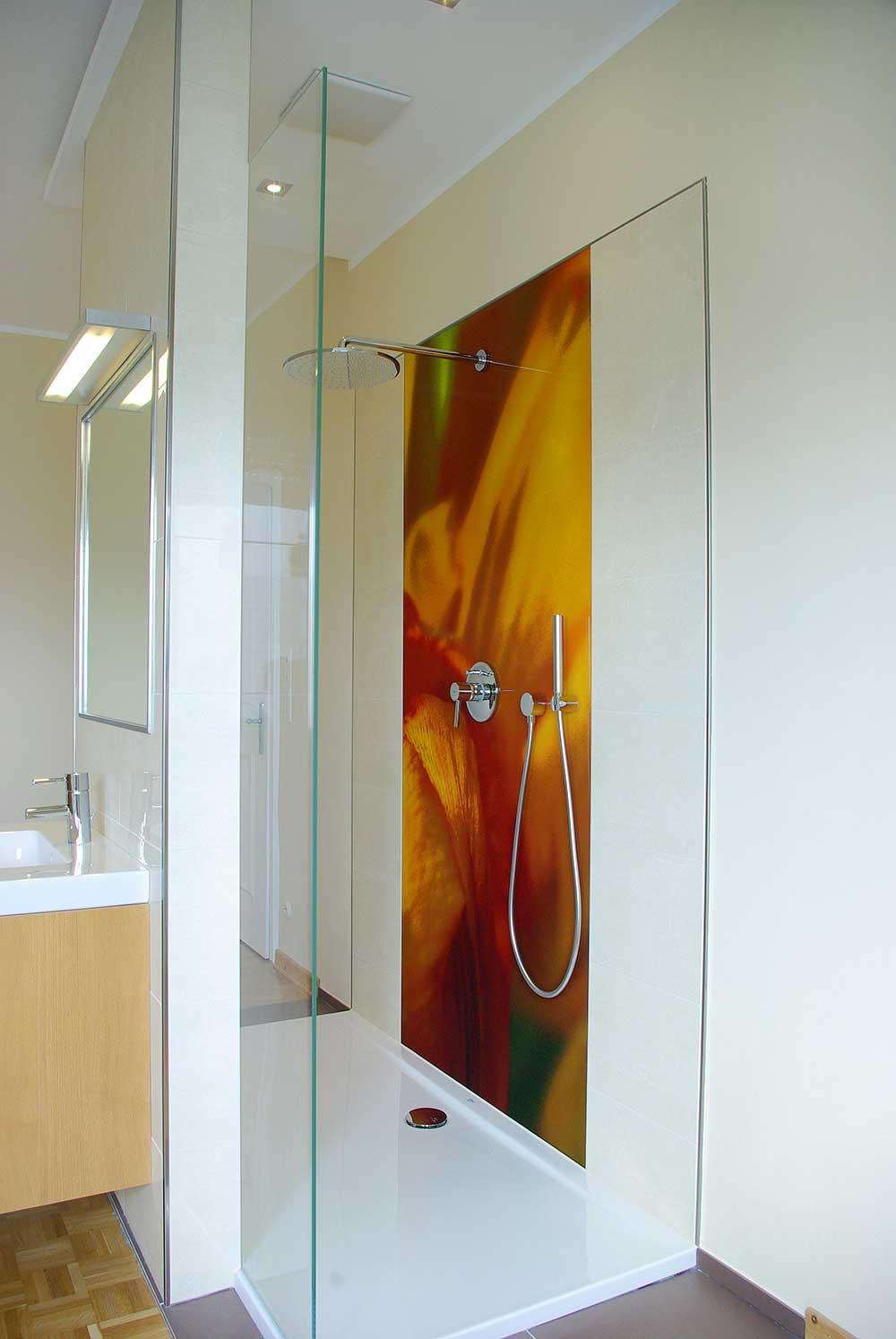 Farbige Duschrückwand in einer offenen, begehbaren Dusche aus bedrucktem Sicherheitsglas, nach einem individuell gestalteten Entwurf von Blüten inspiriert.