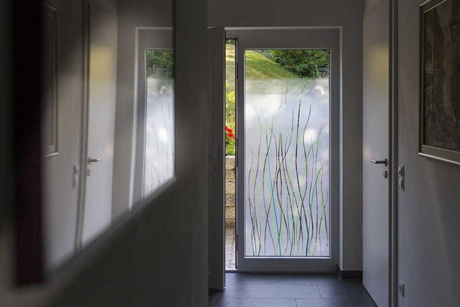 Blick von einem Flur nach draußen. Das Seitenfeld der Eingangstüre ist mit einem Design aus grünen Farbglas-Gräsern und einer verlaufenden Mattierung gestaltet. Im oberen Bereich ist die Scheibe klar.