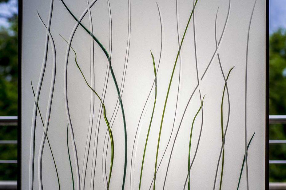 Bild einer Isolierverglasung mit am Brenner geschmolzenen grünen Gräsern auf einem mattierten Glas, das klare Grasstreifen hat. Die Beleuchtung ist von hinten.