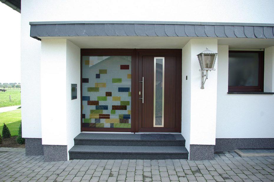Eine Haus-Eingangstüre mit einem Seitenfeld aus einem Design aus farbigen Rechtecken in Rot, Gelb Grün und Blau, kombiniert mit mattiertem Glasfeldern.