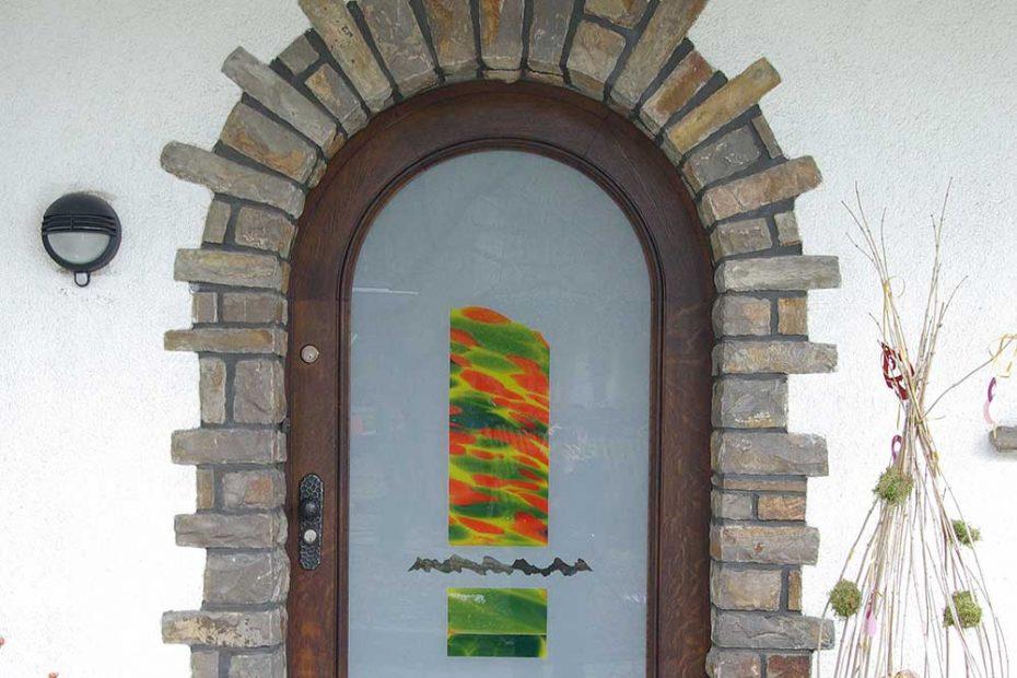 Eine Haus-Eingangstüre mit einem großen Glasfeld. Die Türe ist aus einem mattierten Glas mit einem mundgeblasenen mehrfarben Überfangglas in den Farben Gelb, Organe und Grün.