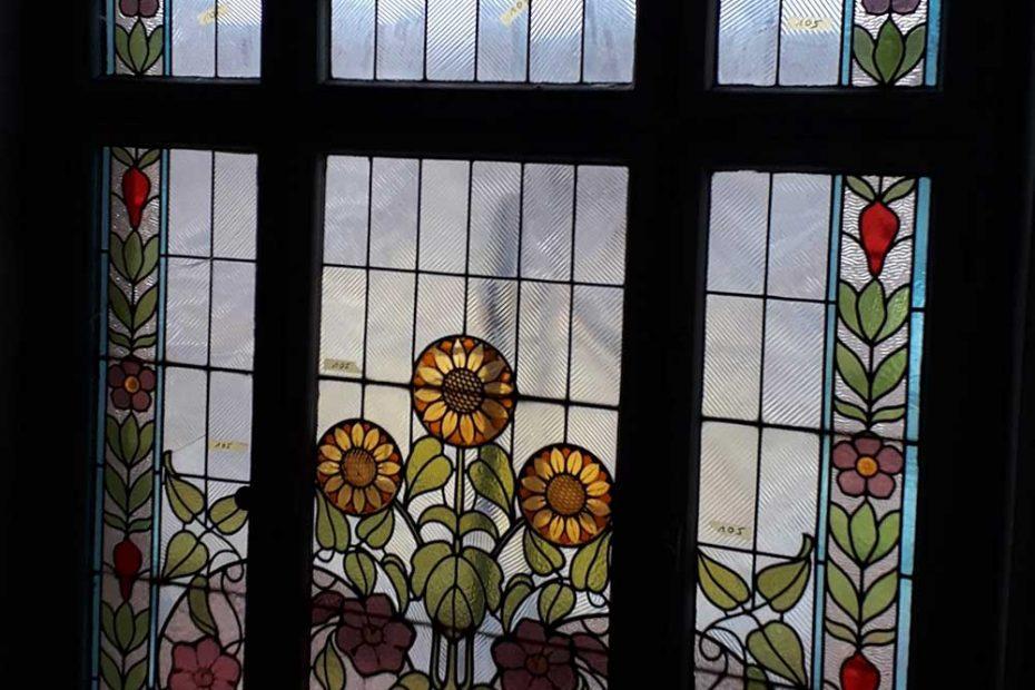 Ein Jugendstilfenster in einem Treppenhaus, das repariert wird.