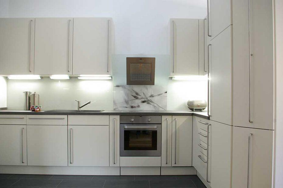 Eine weiße Küche mit einer Küchenrückwand aus weiß lackierten Glas. Hinter dem Herd ist die Glasrückwand mit einem Muster von schwarz/weißen Gräsern bedruckt.