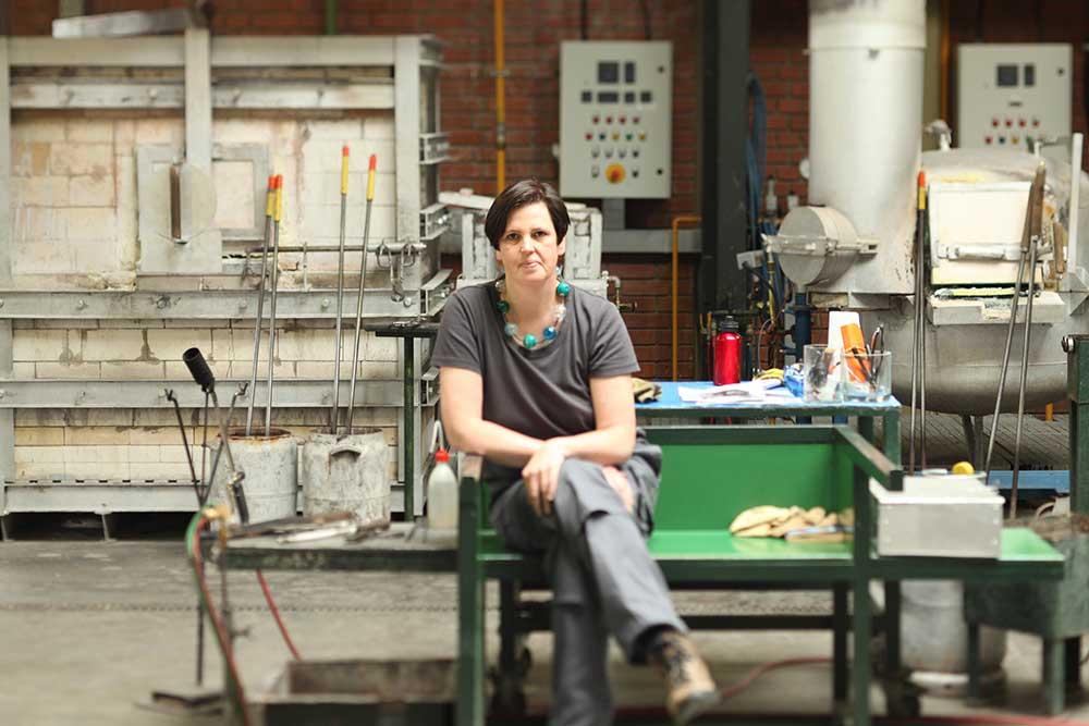 Michaela Maria Moeller sitzt auf einer Glasbläserbank in einem Heißglasstudio.