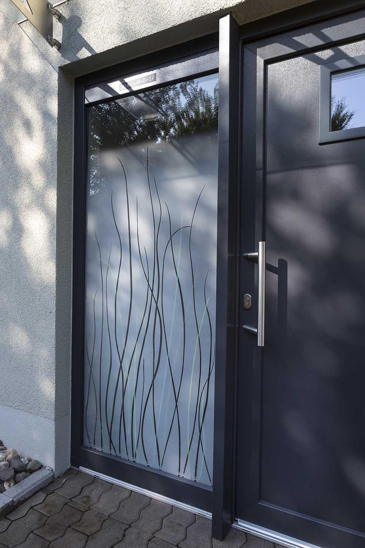 Das Seitenfeld der Haus-Eingangstüre ist mit einem Design aus grünen Farbglas-Gräsern und einer verlaufenden Mattierung gestaltet. Im oberen Bereich ist die Scheibe klar, nach unten hin matt verlaufend. Die Scheibe erfüllt die Richtlinien der Wärmedämmung.